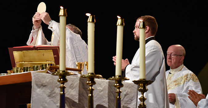 Bishop Olson elevates host at 50th Anniversary Mass