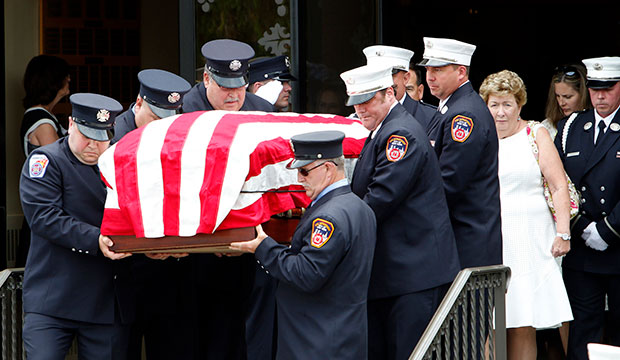 Theresa Stack stands behind the casket with remains of her husband, Battalion Chief Lawrence T. Stack of the New York Fire Department, as it is carried from Sts. Philip & James Church in St. James, N.Y., June 17, 2016.
