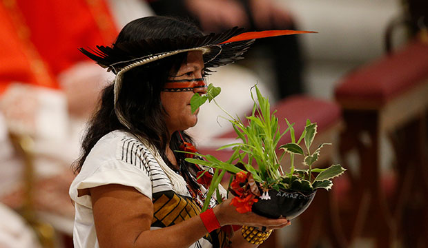 Marcivana Rodrigues Paiva, representing the Satere-Mawe indigenous people in Brazil, carries a plant in the offertory procession as Pope Francis celebrates the concluding Mass of the Synod of Bishops for the Amazon at the Vatican Oct. 27, 2019.