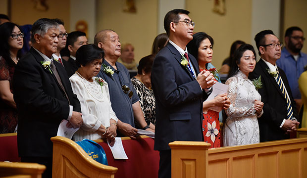 Hieu Le, center, and Yenvy Mang, right of him, stand with other parishioners as Bishop Michael Olson enters to celebrate the Milestone Anniversary Mass at Our Lady Fatima Parish in Fort Worth, Feb. 16, 2020.