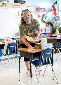 Teacher Cindy Huckabee wipes a desk