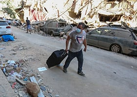 man with suitcase walks on destroyed Beirut street