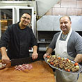 Palestinian Melkite Catholics Peter and Eli Hosh prepare meat in the kitchen of their restaurant, Abu Eli, in Bethlehem, West Bank,