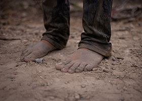 a migrant's bare feet on riverbank