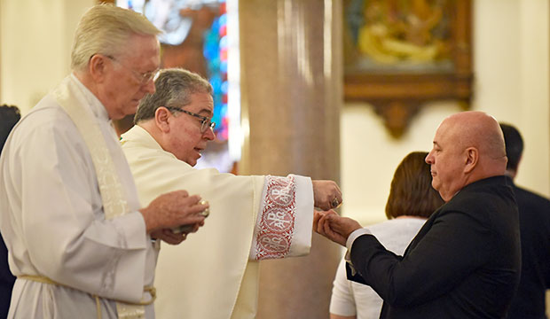 Bishop Michael Olson distributes the Eucharist to a deacon candidate during the Institution of Lectors Mass at Saint Patrick Cathedral in Fort Worth, Saturday, Sept. 30, 2017.