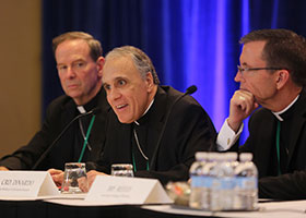 Cardinal Daniel N. DiNardo of Galveston-Houston, president of the U.S. Conference of Catholic Bishops, smiles during a news conference at the fall general assembly of the USCCB in Baltimore Nov. 11, 2019. Also pictured are: Bishop Michael F. Burbidge of Arlington, Va., and Auxiliary Bishop Robert P. Reed of Boston.