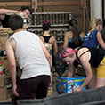 Volunteers unload supplies including diapers, baby wipes, water, soap, rosary beads, Chapstick and other basic items at an immigrant respite center July 13, 2019, in McAllen, Texas.