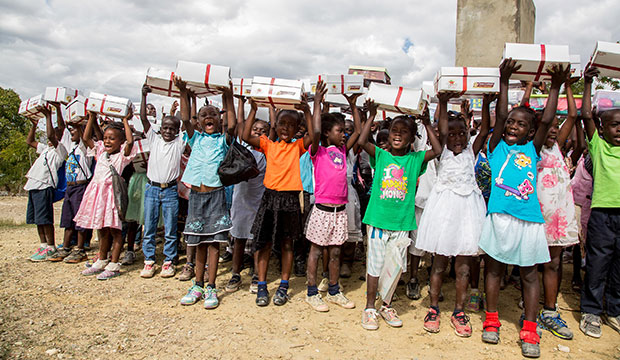 "Children at a school in Mathebonite, Haiti, hold up a ""Box of Joy"" they each received for Christmas."