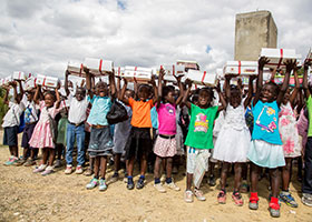 "Children at a school in Mathebonite, Haiti, hold up a ""Box of Joy"" they each received for Christmas in this undated photo."