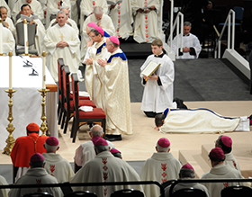 "Bishop-elect Michael Olson lies prostrate before the altar during the ""Litany of Saints"" immediately before his ordination as bishop. In front of him are principal consecrator Archbishop Garcia-Siller (center), and principal co-consecrators Archbishop Emeritus Joseph Fiorenza of Galveston-Houston (left) and Bishop Vann (right)."