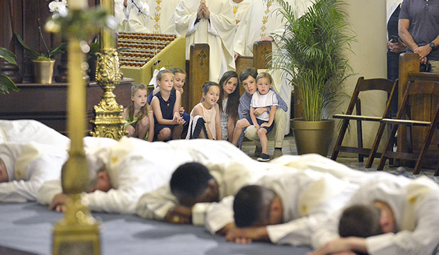 Children from St. Catherine of Siena Parish in Metairie, La., watch eight ordinands to the priesthood lie prostrate for the litany of the saints at their ordination Mass at St. Louis Cathedral in New Orleans June 1, 2019. (CNS photo/Frank J. Methe, Clarion Herald)