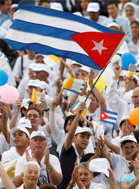 young man waves Cuba's flag during the visit of Pope Benedict XVI to Cuba last year in March. A 55-member Cuban delegation is headed to Rio de Janeiro to mark World Youth Day. (CNS photo/Paul Haring)