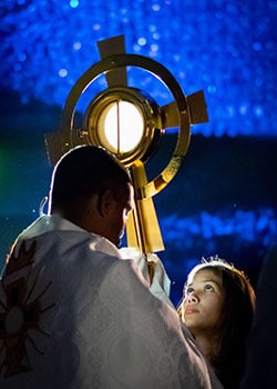 girl looking up at monstrance