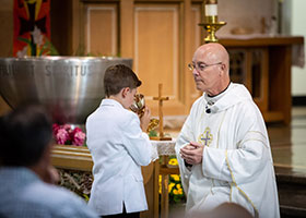 Father Ken Robinson gives first communion to Zach Schilling at Sacred Heart Catholic Church in Muenster, Texas on Sunday, May 26, 2019. (Photo by Kevin Bartram)