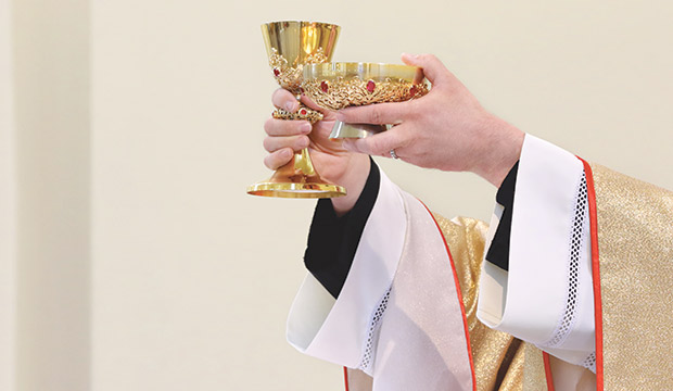 a priest's hands elevate the chalice and paten