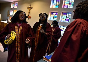 Agatha Agyemang, left, and Nichole Dadzie, sing and dance during a song by the Ghanaian choir during Sunday Mass at St. Joseph Parish in Arlington, March 17. (NTC/Ben Torres)