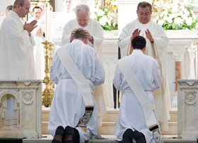 Fr. Kyle Walterscheid looks on as priests lay hands on the newly ordained Fr. Michael Moloney and Fr. Manuel Holguin, at St. Patrick Cathedral June 9. (NTC Photo/Juan Guajardo).