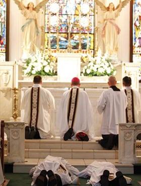 Deacons Manuel Holguin (right) and Michael Moloney prostrate themselves before the altar of St. Patrick Cathedral as the Litany of the Saints is sung, just before Bishop Kevin Vann ordains them to the priesthood for the Diocese of Fort Worth, Saturday, June 9.