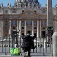 A man prays at an empty St. Peter's square