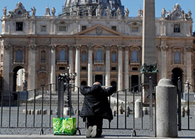 A man prays in front of an empty St. Peter's Square in Rome March 25, 2020.