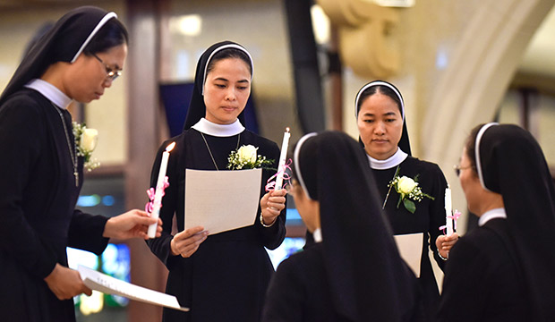 Three sisters, of a group of nine from the Lovers of the Holy Cross order, renew their vows at  Vietnamese Martyrs Parish