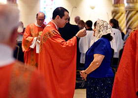 Fr. Jonathan Demma distributes the Eucharist to his mother Alana Demma at his first Mass as a priest at St. Elizabeth Ann Seton Church in Keller, May 19, 2018.