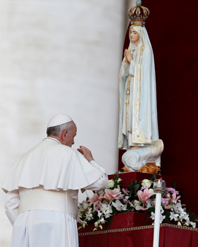 Pope Francis makes the sign of the cross as he prays in front of the original statue of Our Lady of Fatima during a Marian vigil in St. Peter's Square at the Vatican Oct. 12. The statue was brought from Portugal for a weekend of Marian events culminating in Pope Francis consecrating the world to Mary. (CNS photo/Paul Haring)