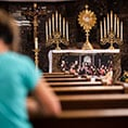 An adorer kneels before the Blessed Sacrament inside St. Peter's perpetual Adoration chapel