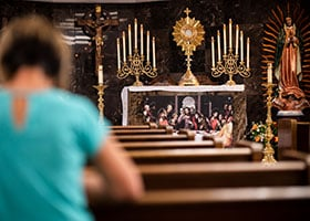 An adorer kneels before the Blessed Sacrament inside St. Peter's perpetual Adoration chapel.