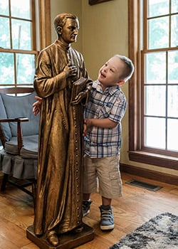 Mikey Schachle, 5, examines a statue of Father Michael McGivney at the home where he lives with his parents, Daniel and Michelle, and siblings in Dickson, Tenn., June 2, 2020. e Knights of Columbus, to intercede with God to save their son, still in his mother's womb, who was given no hope of surviving a life-threatening case of fetal hydrops. (CNS photo/Rick Musacchio, Tennessee Register)