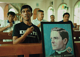 Jeffrey Rentegrado leads the rosary with other members of the Knights of Columbus in the Philippines alongside a portrait of the Knights' founder, Father Michael J. McGivney, in 2019.