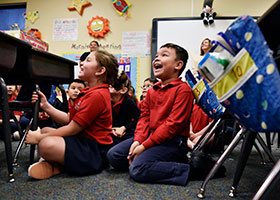 Aidan Vasquez, right, reacts with joy as Joe Daniels and Marc Wolf thanked students for their art work and letters honoring Veterans, during a visit to St. Joseph Catholic School in Arlington, Nov. 07, 2019.
