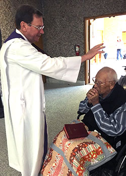 Father Jack McKone blesses Moses Lopez on his 99th birthday