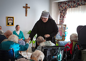 Sister Constance Veit, a Little Sister of the Poor, collects rosaries from elderly residents following prayers at the Jeanne Jugan Residence for senior care in Washington March 25, 2019. Sister Constance is considered a spiritual mother by many of the residents, who said they will honor her on Mother's Day. (CNS photo/Chaz Muth)