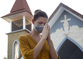 woman prays in front of church