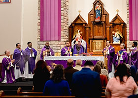 Bishop Michael Olson elevates the Body of Christ during consecration at Our Lady Queen of Peace Parish