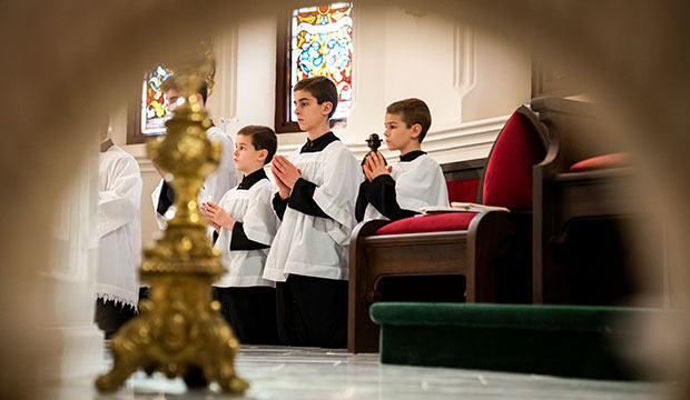 Altar servers kneel during the Liturgy of the Eucharist