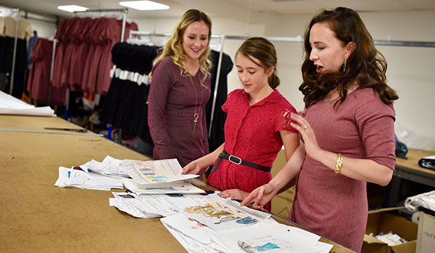 Sisters Mary Kunkel, left, volunteer Sophia Kunkel and Audrey Cole, right, of Paris Bloom, look over illustrations their younger sister Sophia made for possible dress lines for Paris Bloom, photographed at TLCI Manufacturing in Dallas. (NTC/Ben Torres)