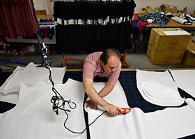 Jose Portillo, owner of TLCI Manufacturing, cuts sheets of paper containing dress patters before making cuts to fabric for a dress at his shop in Dallas