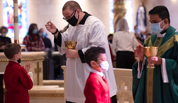 Seminarian Brandon LeClair distributes Communion