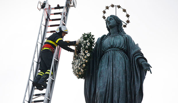 A firefighter places a wreath on a Marian statue overlooking the Spanish Steps in Rome Dec. 8, 2019, the feast of the Immaculate Conception. (CNS photo/Paul Haring)