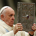 Pope Francis holds the Book of Gospels