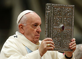 Pope Francis holds book of Gospel