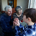 Grandparents interact with their grandchildren through a window