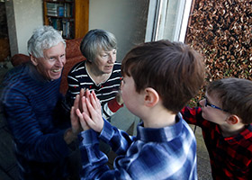 grandparents and grandchildren interact through window