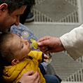 Pope Francis puts a pacifier in a baby's mouth.