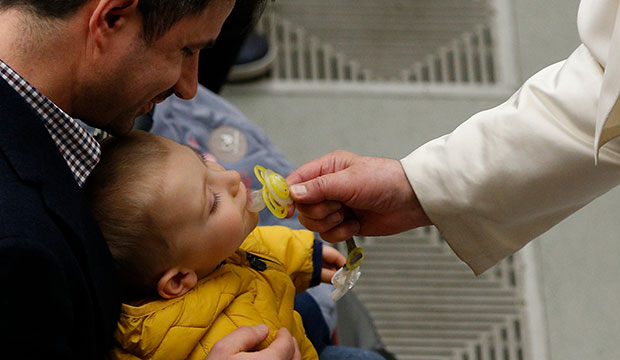 Pope Francis puts a pacifier in a baby's mouth during his general audience in Paul VI hall at the Vatican Feb. 19, 2020. (CNS photo/Paul Haring)