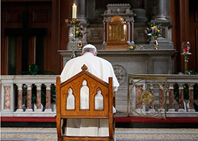 Pope Francis prays in front of a candle in memory of victims of sexual abuse as he visits St. Mary's Pro-Cathedral in Dublin Aug. 25, 2018. Pope Francis has revised and clarified norms and procedures for holding bishops and religious superiors accountable in protecting minors as well as in protecting members of religious orders and seminarians from abuse. (CNS photo/Paul Haring)