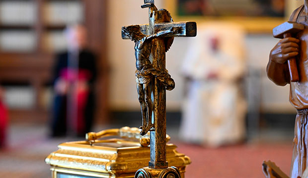 crucifix with pope in background