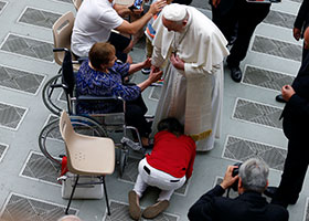 Pope Francis greets a disabled pilgrim during his general audience in Paul VI hall at the Vatican Aug. 7, 2019.